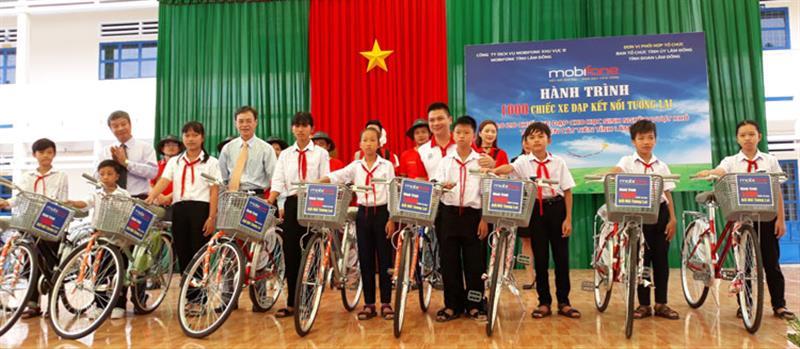 Trưởng Ban Tổ chức Tỉnh ủy Trần Duy Hùng và lãnh đạo huyện Cát Tiên, đại diện MobiFone tỉnh Lâm Đồng trao tặng xe đạp cho các em học sinh. Ảnh: NGÂN HẬU