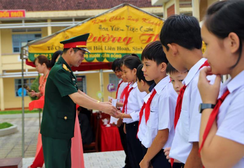 Đại tá Nguyễn Bình Sơn - UVBTV Tỉnh ủy, Chỉ huy trưởng Bộ Chỉ huy Quân sự tỉnh Lâm Đồng tặng học bổng cho các em học sinh nghèo. Ảnh: KHÁNH PHÚC