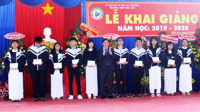 Đồng chí Nguyễn Văn Triệu trao học bổng cho các em học sinh nghèo vượt khó. Ảnh: KHÁNH PHÚC
